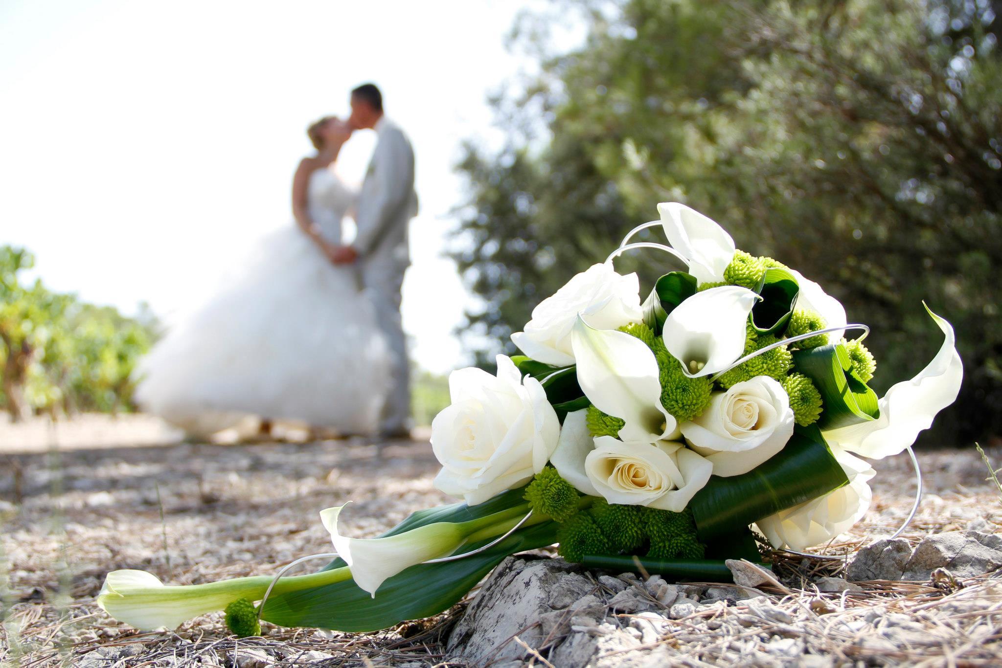 Photo mariage bouquet net devant mariés flous derrière